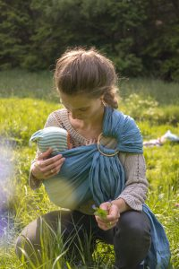 mother cuddeling a newborn baby in a babywearing sling
